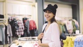 少女在镜子前面的一家商店试穿一个帽子 影视素材