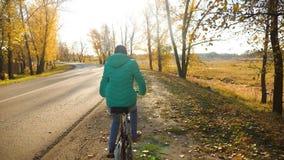 少女在黄色树背景的骑马自行车在秋天公园 影视素材