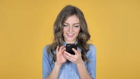 少女在黄色背景隔绝的浏览智能手机 股票视频