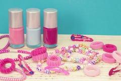 少女少年室,构成的地方在家 一个小组五颜六色的指甲油瓶,头发丝带,镯子,项链,头发 图库摄影