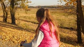 少女有长发的和桃红色夹克骑马自行车的在秋天公园 慢的行动 股票录像