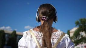 少女步行沿着向下有耳机的一条城市街道并且听到音乐 白色礼服的少年女孩有长发的 股票录像
