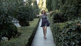 少女沿有绿叶的一个美丽的胡同走,当她看见时照相机乐趣跑往她 股票录像