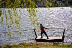 少女沿木筏和绳索的江边拉扯自己 免版税库存图片