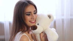 少女特写镜头画象有长发的有在窗口附近的一个玩具熊的 影视素材
