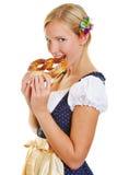 少女装的妇女咬住在椒盐脆饼的 免版税库存图片