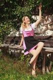 少女装的快乐的妇女在长凳 免版税库存图片