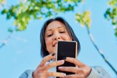少女谈话在智能手机和键入的消息与智能手机 免版税库存图片