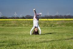 少女跳跃在草的,具有体育性质的一个女孩 自然的女孩做特技动作 免版税库存照片
