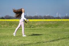 少女跳跃在草的,具有体育性质的一个女孩 自然的女孩做特技动作 库存照片