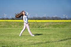 少女跳跃在草的,具有体育性质的一个女孩 自然的女孩做特技动作 免版税图库摄影