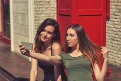 少女采取selfies使用在城市的街道上的一个手机 库存图片