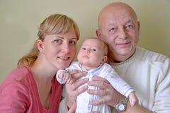 少妇、祖父和婴孩 3个照相机长沙发系列女孩查找关于坐的母亲橙色纵向他们那里 免版税库存照片