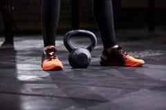 少妇、腿在黑绑腿,橙色运动鞋和kettlebell的播种的图象 Crossfit锻炼 免版税图库摄影