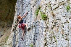 少妇上升在洞的攀岩运动员 免版税库存照片