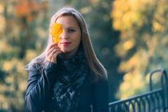 少妇与一片黄色橡木叶子的覆盖物眼睛 免版税库存照片