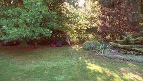 少妇与在自己的绿色庭院的割草机一起使用 4K 股票视频