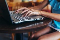 少妇与坐在咖啡馆的膝上型计算机一起使用 库存图片