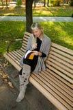 少妇与铅笔的阅读书在手中在澳大利亚的一条长凳 免版税库存照片