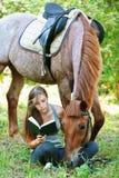 少妇与马的阅读书 免版税库存照片