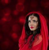 少妇东方样式画象红色的在抽象背景 免版税图库摄影
