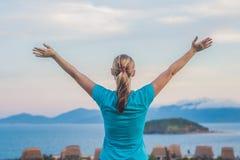 少妇举了她的手由太阳决定,反对海、岩石和天空与云彩 免版税图库摄影