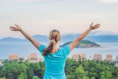 少妇举了她的手由太阳决定,反对海、岩石和天空与云彩 库存照片