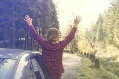 少妇举她的胳膊对倾斜在车窗外面的天空 库存图片