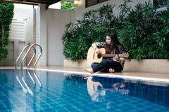 少妇举行吉他经典之作在她的手上和坐在p旁边 库存照片