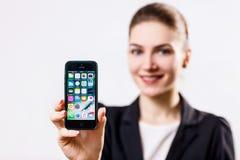 少妇举行黑苹果计算机iPhone 5在手中显示 库存照片
