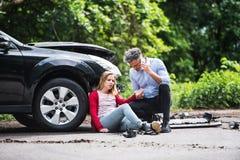 少妇乘在打电话的事故和一个人以后的汽车 免版税库存照片