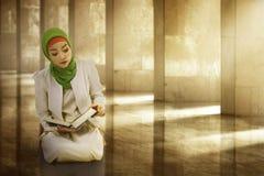 少妇亚裔穆斯林佩带的hijab,读koran 免版税库存照片