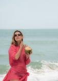 少妇享用在海滩的椰子鸡尾酒 免版税库存图片