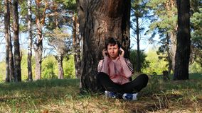 少妇休息的坐由一棵树在公园和听到音乐通过耳机 音乐,室外休闲 股票视频