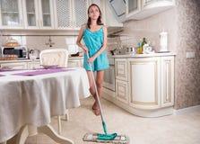 少妇作白日梦的和擦的厨房地板 免版税库存照片
