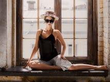 少妇佩带的白色短裤、黑上面、帽子和太阳镜 库存照片