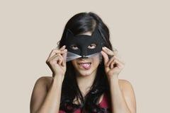 少妇佩带的眼罩的画象,当在色的背景时的尖酸的嘴唇 库存图片