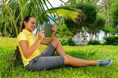 少妇侧视图草坪的有她的片剂计算机的 库存照片