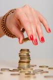 少妇修造的硬币堆 免版税库存照片