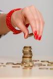 少妇修造的硬币堆 免版税库存图片