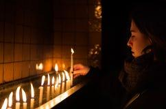 少妇光每蜡烛在教会里 库存照片