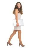 少妇全长画象有去的膝上型计算机的斜向一边 免版税库存图片