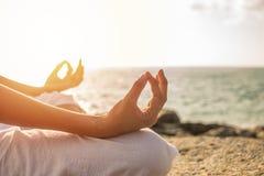 少妇凝思在热带海滩的瑜伽姿势与阳光 库存照片