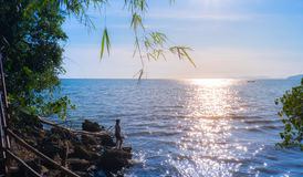 少妇剪影享用与在海滩的日落和微笑对太阳 库存图片