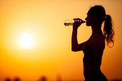少妇剪影喝水反对日落背景 图库摄影