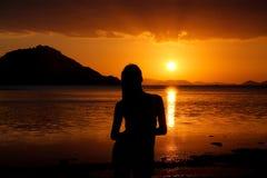 少妇剪影日落的在kanawa海岛,印度尼西亚 免版税图库摄影