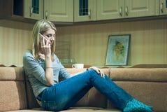 少妇单独坐和谈话在电话 免版税库存图片