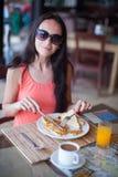 少妇吃早餐在手段餐馆 免版税库存图片