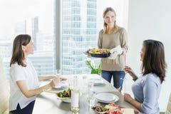 少妇吃晚餐一起在现代厨房 免版税图库摄影