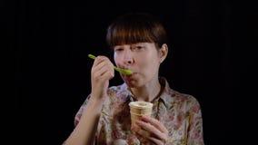 少妇吃着与一把匙子的冰淇凌在黑背景 股票视频
